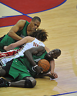 Rajon Rondo, back, and Kevin Garnett battle for a rebound against Anderson Varejao.