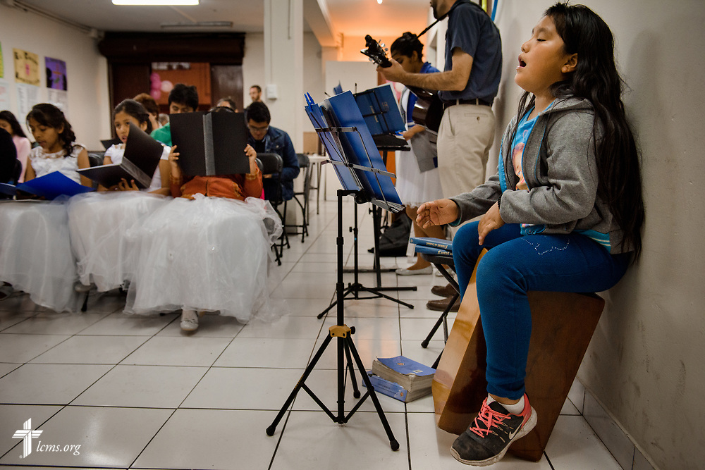 A young member of Castillo Fuerte uses a traditional instrument similar to a drum for evening worship with confirmations at Castillo Fuerte on Saturday, Nov. 4, 2017, in the La Victoria district of Lima, Peru. LCMS Communications/Erik M. Lunsford