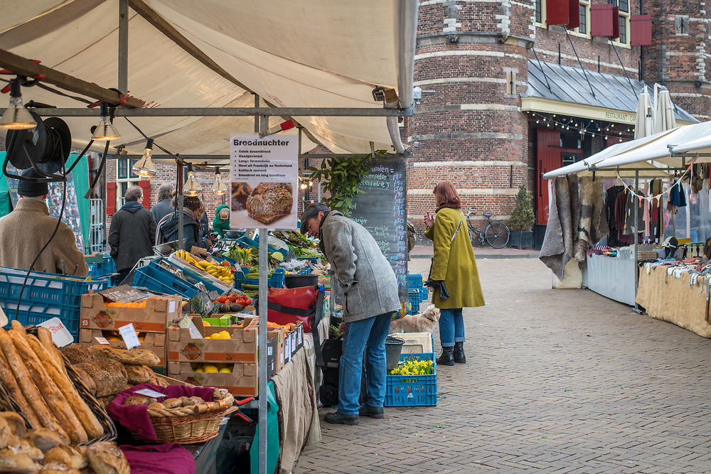 Shoppers browse the goods for sale at outdoor market, Amsterdam, Netherlands