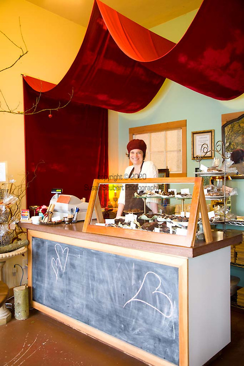 "Sarah Hart, owner Alma Chocolates, behind the register at her botique chocolate shop in Portland, Oregon. She creates ""Day of the Dead"" sweets among other ornate confections."