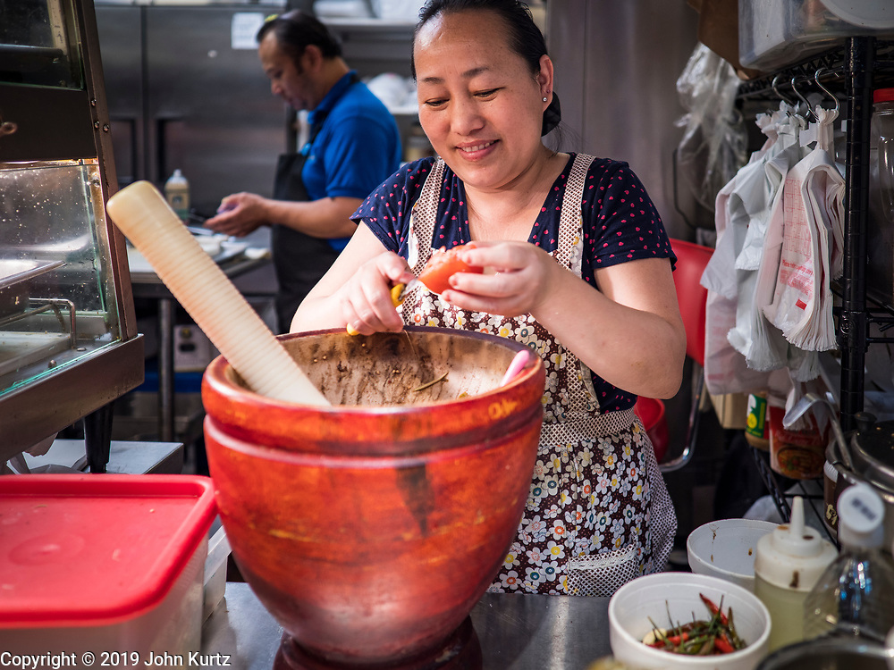 03 AUGUST 2019 - ST. PAUL, MINNESOTA: A woman makes Lao som-tam (papaya salad) in the food court at the Hmong Village shopping center. Thousands of Hmong people, originally from the mountains of central Laos, settled in the Twin Cities in the late 1970s and early 1980s. Most were refugees displaced by the American war in Southeast Asia. According to the 2010 U.S. Census, there are now 66,000 ethnic Hmong in the Minneapolis-St. Paul area, making it the largest urban Hmong population in the world. There are two large Hmong markers in St. Paul. The Hmongtown Marketplace has are more than 125 shops, 11 restaurants, and a farmers' market in the summer. Hmong Village is newer and has more than 250 shops and 17 restaurants.    PHOTO BY JACK KURTZ