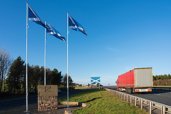 Scottish flags at marker point at Scottish Border on A1 between the Scottish Borders and Northumberland, UK