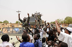 59722709 .Soldiers wave to residents after returning from battlefield, in El Rahad of Sudan's North Kordofan State May 28, 2013. Sudanese army announced on Monday that it has liberated the strategic area of Abu Karshula in South Kordofan State from rebels of the Revolutionary Front. May 28, 2013..UK ONLY
