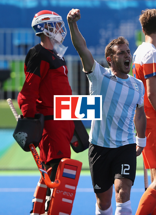 RIO DE JANEIRO, BRAZIL - AUGUST 06:  Lucas Vila #12 of Argentina reacts to scoring as Jaap Stockmann of the Netherlands looks on during the Pool B match between Argentina and Netherlands at Olympic Hockey Centre on August 6, 2016 in Rio de Janeiro, Brazil.  (Photo by Sean M. Haffey/Getty Images)