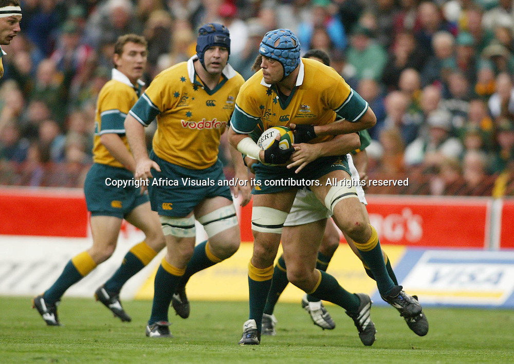 17 August 2002, Ellis Park, Tri - Nations, Rugby Union. South Africa v Australia. Nathan Sharpe looks for support as he is tackled by Bobby Skinstad. The Springboks defeated Australia, 33-31.<br />Pic: Noel Hammond/Photosport