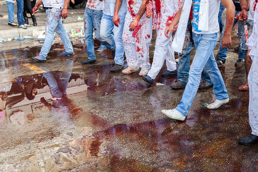 Mourning shiite muslim men, covered in their own blood, carrying traditional knives and swords, marching through the streets of Nabatieh, Lebanon, during the Day of Ashura. (November 14, 2013).