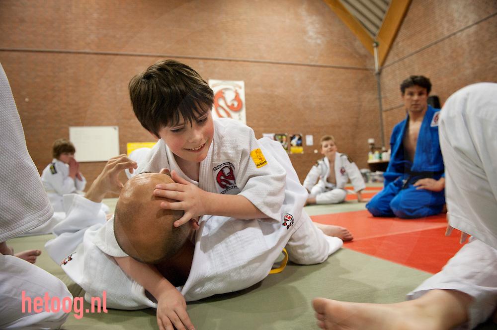 nederland,deventer,11april2012 judo voor kinderen met een beperking. terwijl intructeur Gerbern Koops in een houtgreep gelegd wordt kijkt assistent Mario toe