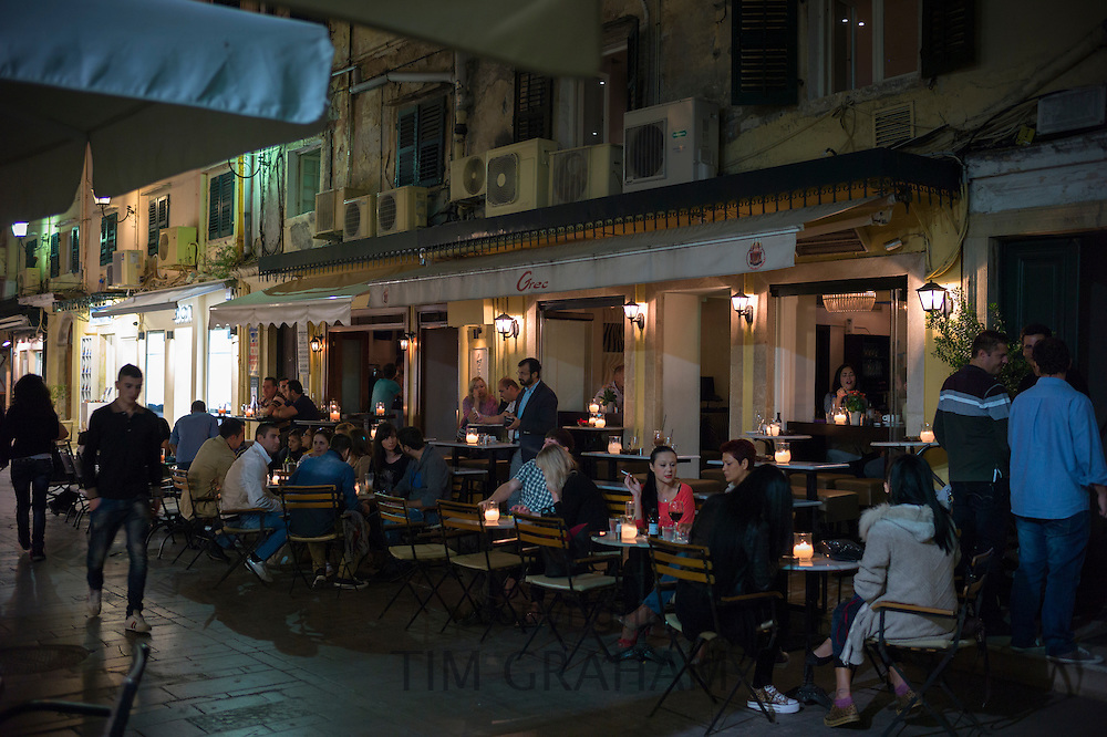 Nighttime cafe society street scene, local people and tourists at pavement cafe bar restaurant in Kerkyra, Corfu, Greece