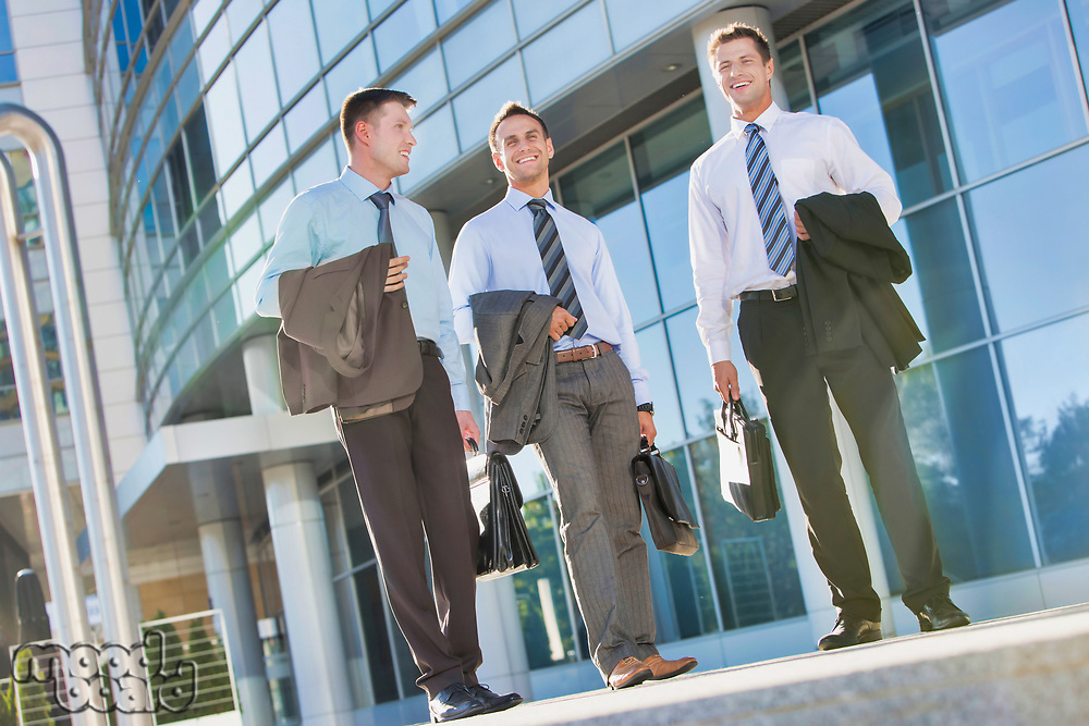 Mature attractive businessmen walking while talking against office building after work