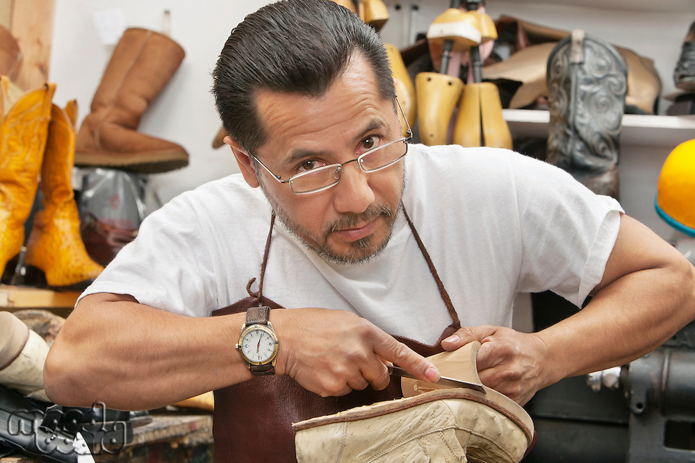 Portrait of a confident shoemaker cutting sole from footwear in workshop