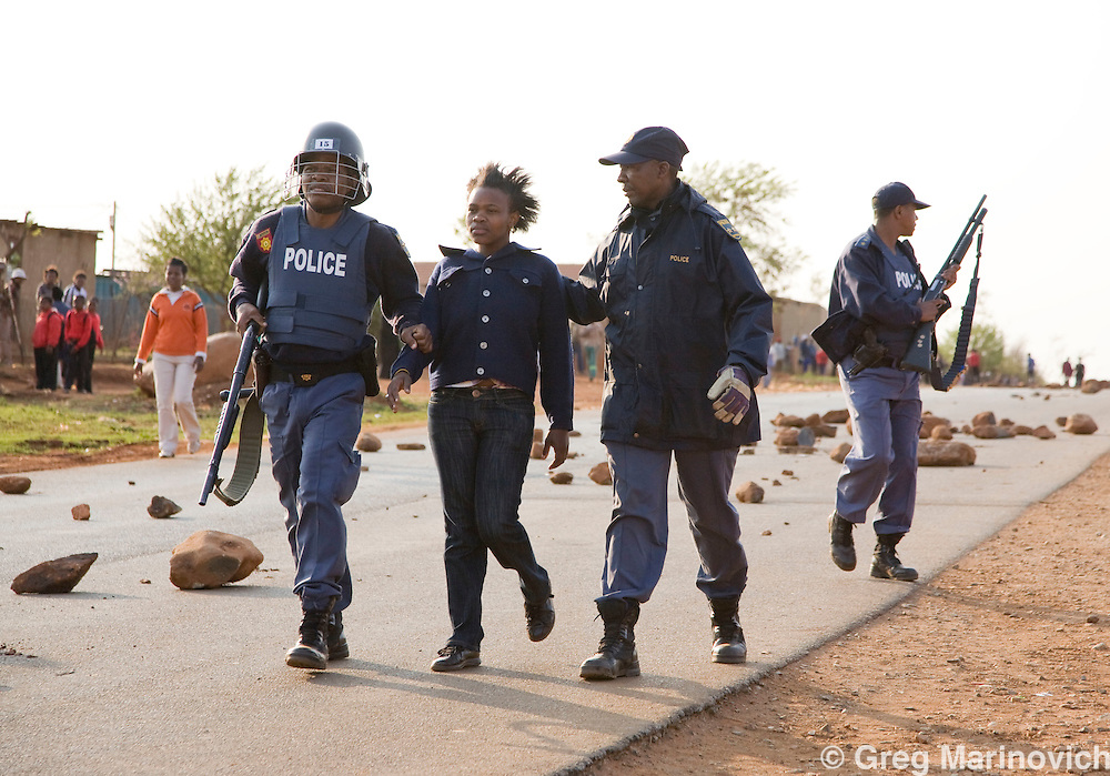 A young woman is arrested after residents of South Africa's largest informal settlement - Orange farm - take to the streets, blocking off a major road to try and get government to take notice of their plight, Sept 2008. Many of the people living in shacks have done so since the earlt 1990's, and many have no potabel water, despite 15 years of a black government. Photo Greg Marinovich