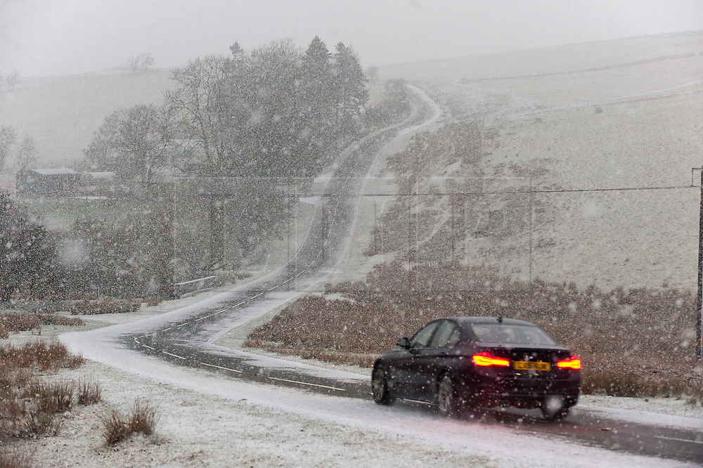 © Licensed to London News Pictures. 18/01/2019. Builth Wells, Powys, Wales, UK. A motorist negotiates the B4520 (Brecon Road) in a wintry landscape on the high moorland of the Mynydd Epynt range near Builth Wells in Powys, Wales, UK Heavy snow hits Powys Wales, UK. credit: Graham M. Lawrence/LNP