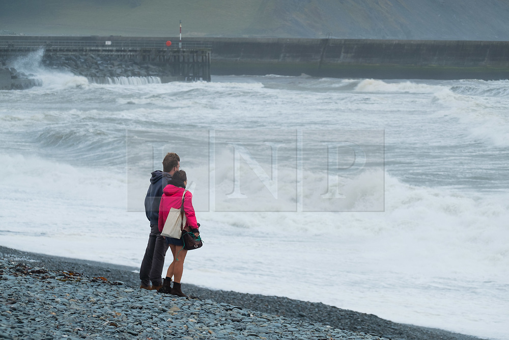 ©Licensed to London News Pictures.10/08/2019 Aberystwyth UK.<br /> Gale force winds gusting to over 50mph and stormy seas batter the harbour lighthouse, and makes life difficult for pedestrians in Aberystwyth as unseasonably wet and windy weather sweeps across much of the west of the UK , bringing severe disruption to travel and forcing the cancellation of many outdoor events. Photo credit Keith Morris/LNP