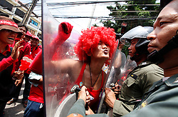 A Thai red shirt protester dressed in a red wig attempts to kiss a riot police officer as protesters march towards the ASEAN summit venue of the Pattaya Exhibition and Convention Hall (PEACH) demanding the current government step down, on the first day of the Association of South East Asian Nations (ASEAN) plus six summit, in Pattaya, Thailand, about 160 km south east of Bangkok, Thailand, 10 April 2009. Thailand hosts the ASEAN plus three and six summits including leaders of China, Japan, South Korea, India, Australia, and New Zealand, with South East Asian leaders, from April 10 to 12.