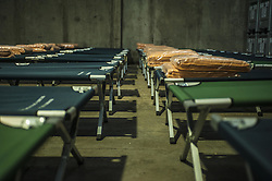 October 23, 2016 - Calais, France - Travel cots are installed in the hangar to accommodate refugees who have not been able to leave that day. 130 seats are ptévues in Calais, France on october 24, 2016...The dismantling of the Calais jungle to begin Monday morning at 8am. The prefecture and the government set up a camp to distribute the refugees to centers all over France.  Calais, France on 23 October 2016. (Credit Image: © Julien Pitinome/NurPhoto via ZUMA Press)