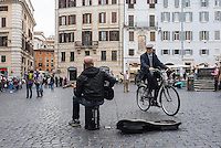 A man plays guitar in a piazza in Rome as another man rides by on a bicycle.