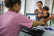 09 JULY 2014 - ARANYAPRATHET, SA KAEO, THAILAND:  A Cambodian migrant worker holds her child while she's fingerprinted for an ID card at the Thai Immigration One Stop Service Center in Aranyaprathet on the Thai-Cambodian border. More than 200,000 Cambodian migrant workers, most undocumented, fled Thailand in early June fearing a crackdown by Thai authorities after a coup unseated the elected government. Employers have been unable to fill the vacancies created by the Cambodian exodus and the Thai government has allowed them to return. The Cambodian workers have to have a job and their employers have to vouch for them. The Thai government is issuing temporary ID cards to allow them to travel openly to their jobs. About 800 Cambodian workers came back to Thailand through the Aranyaprathet border crossing Wednesday. The Thai government has opening similar service centers at three other crossing points on the Thai-Cambodian border.   PHOTO BY JACK KURTZ