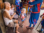 30 OCTOBER 2014 - BANGKOK, THAILAND: An elderly man jokes with Chinese traditional dancers during the parade marking the start of the annual temple fair at Wat Saket. Wat Saket is on a man-made hill in the historic section of Bangkok. The temple has golden spire that is 260 feet high which was the highest point in Bangkok for more than 100 years. The temple construction began in the 1800s in the reign of King Rama III and was completed in the reign of King Rama IV. The annual temple fair is held on the 12th lunar month, for nine days around the November full moon. During the fair a red cloth (reminiscent of a monk's robe) is placed around the Golden Mount while the temple grounds hosts Thai traditional theatre, food stalls and traditional shows.   PHOTO BY JACK KURTZ