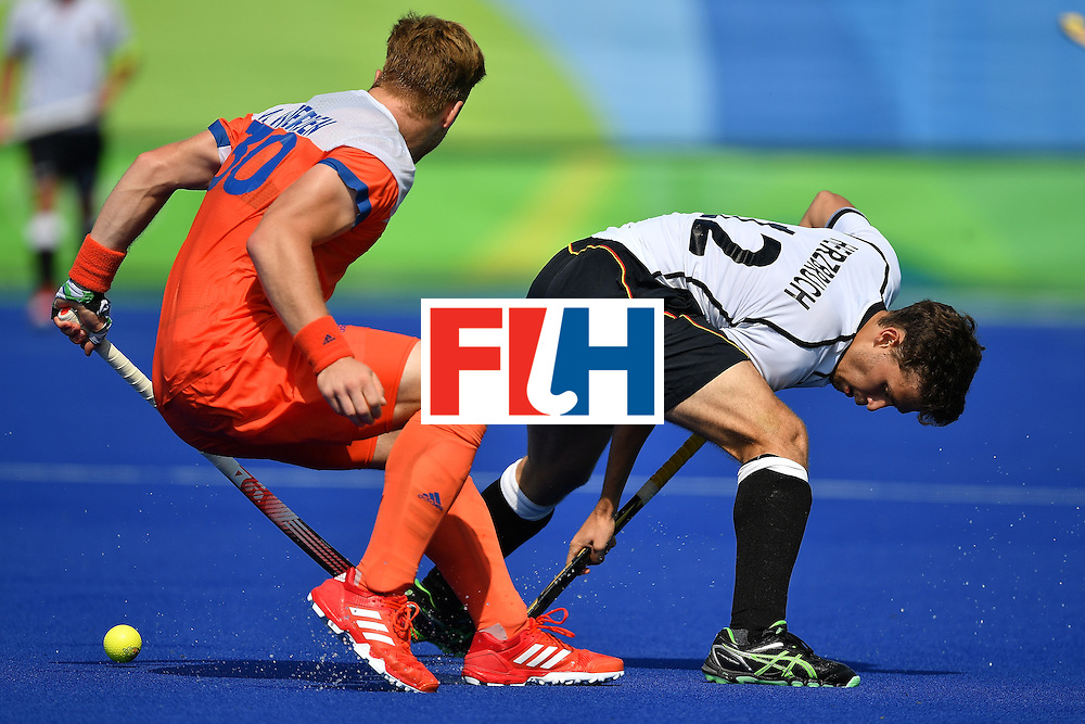 RIO DE JANEIRO, BRAZIL - AUGUST 18:  Player Timm Herbruch (R) of Germany contests the ball with Mink Van Der Weerden of the Netherlands during the Hockey Bronze medal match in the Olympic Hockey centre on Day 13 of the Olympic games on August 18, 2016 in Rio de Janeiro, Brazil.  (Photo by Pascal Le Segretain/Getty Images)