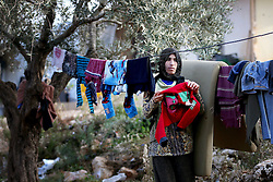 A Syrian refugee woman hangs out her washing in a settlement camp where she lives amongst an olive grove in Koura, near Tripoli, Lebanon.