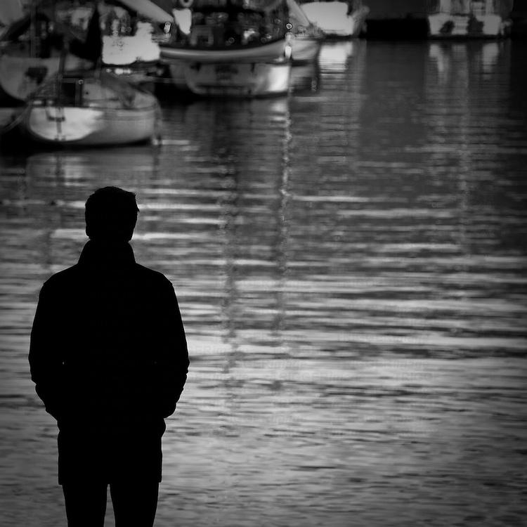A very sharp silhouette of a man against a marina in Deep Cove.