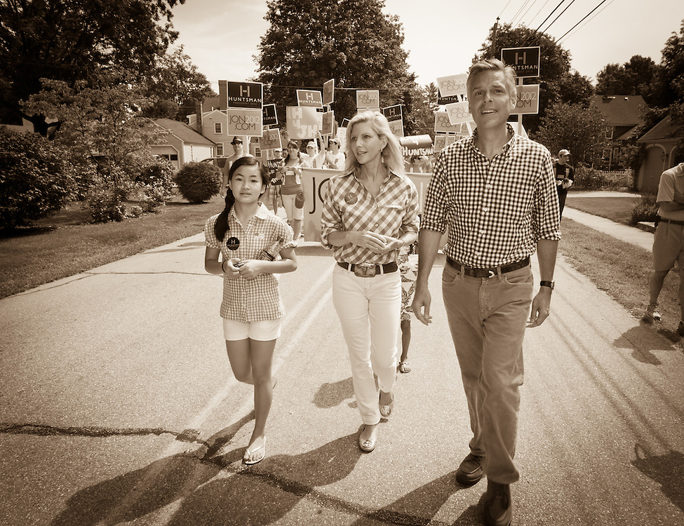 Jon Huntsman, his wife Mary Kaye and daughters Asha Bharati and Gracie Mei, wave to the crowd along the parade route, during the July 4th parade in Amherst, NH.