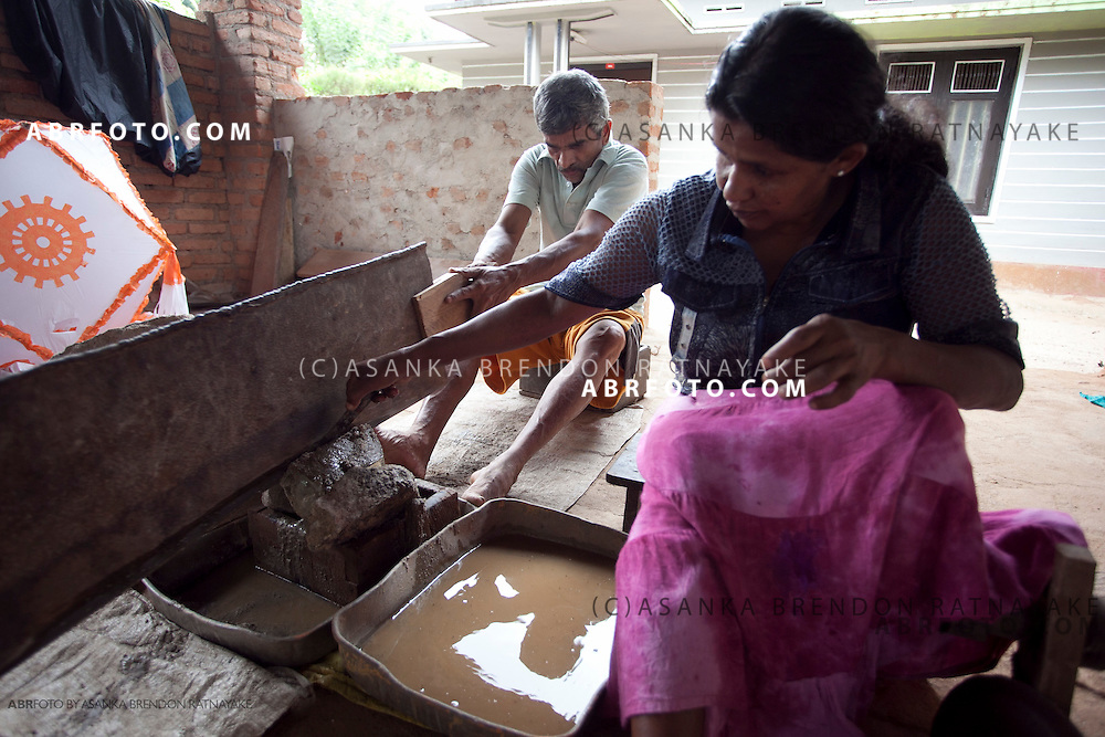 Mr Gunasoma, is assisted by his wife in cutting up a large piece of quartz.