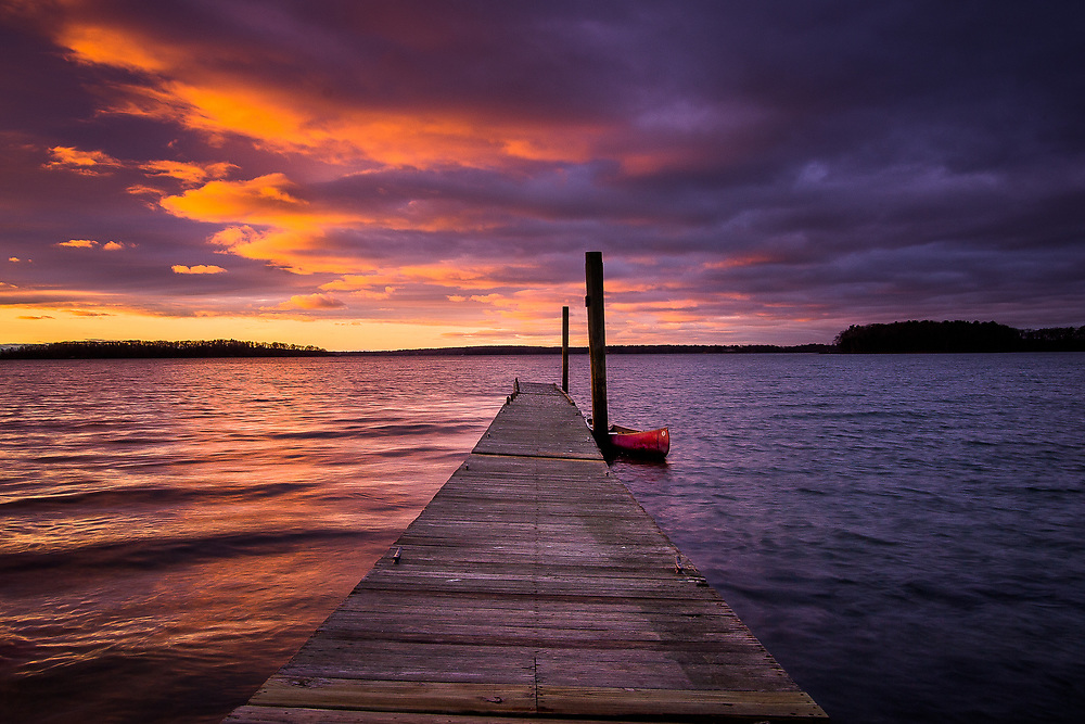 A red canoe is tied up to the pier under a beautiful sunrise sky at Freeport's Winslow Park.