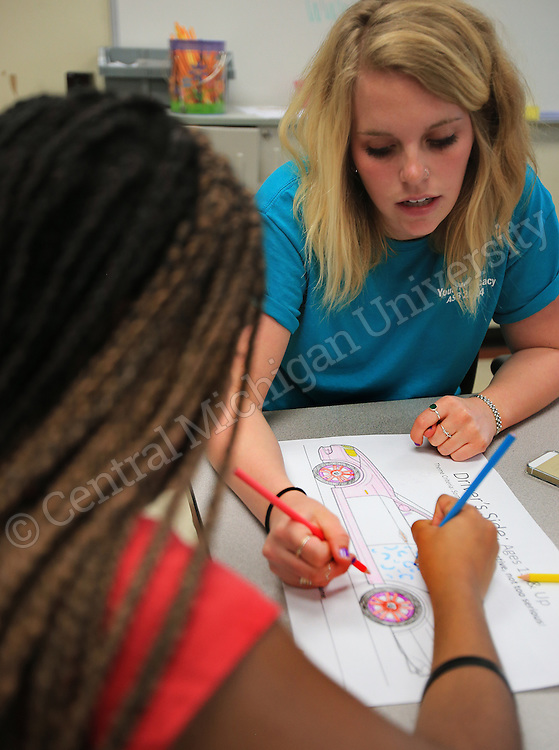 Elyse Courtright, of Dearborn, works with a student tutoring after school (Kids were not allowed to be named or faces photographed). She was among eleven CMU students volunteering during her Alternative Break at the Carolina Youth Development Center in North Charleston, SC, spending the week to help with projects to improve the center and in the community.  CMU is ranked fourth in the nation for the number of students participating in Alternative Breaks and fifth in the country for the most trips coordinated by a university. The program organizes about 40 trips each year with more than 400 students participating. Photo by Steve Jessmore/Central Michigan University