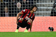 Nathan Ake (5) of AFC Bournemouth goes down holds his calf after injuring himself after making a goal saving tackle on Mohamed Salah (11) of Liverpool during the Premier League match between Bournemouth and Liverpool at the Vitality Stadium, Bournemouth, England on 7 December 2019.