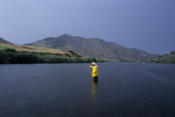 Stock photo of a man wading and fishing from the middle of a river