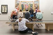 Belgie, Brugge, 20140605.<br /> Studenten maken een opdracht in het Groeninge Museum in Brugge. De studenten zitten op klapstoeltjes en op de grond. Ze staan voor een triptiek van Memling<br /> <br /> Belgium, Bruges, 20140605.<br /> Students create a command from the Groeninge Museum in Bruges. The students sit on folding chairs and on the ground. They stand for a triptych by Memling<br /> Summer Course 2014 Emerson College