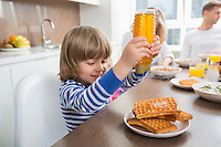 Happy boy pouring honey on waffles while having breakfast with family