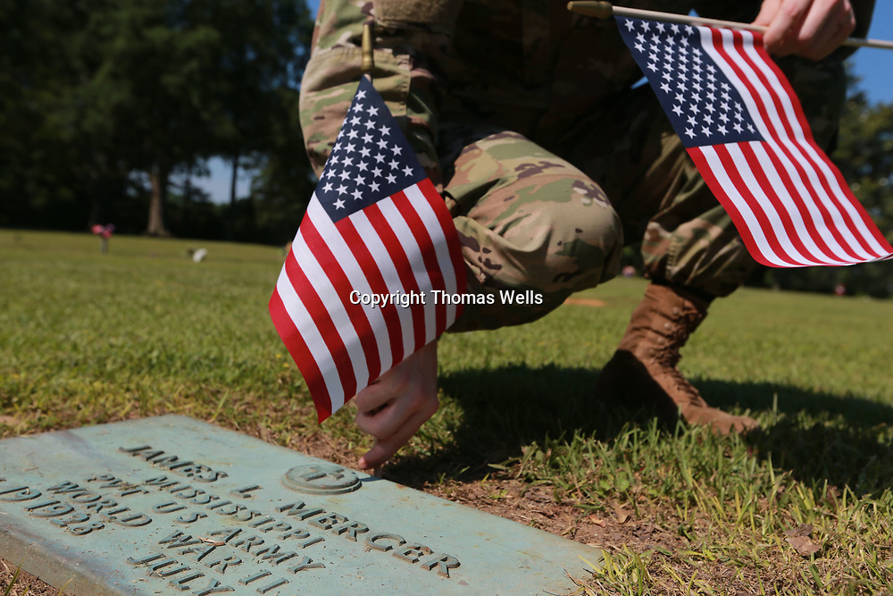 Sgt. Vincent Huggins of the 834th Aviation Support Battalion places another flag on the grave of a veteran at Tupelo memoiral Park in Tupelo.