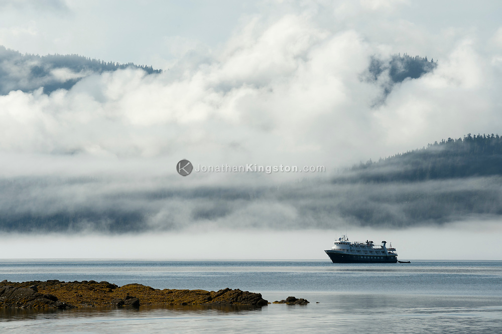 Mountains and fog rise behind a small cruise ship anchored in Saginaw Bay on Alaska's inside passage.