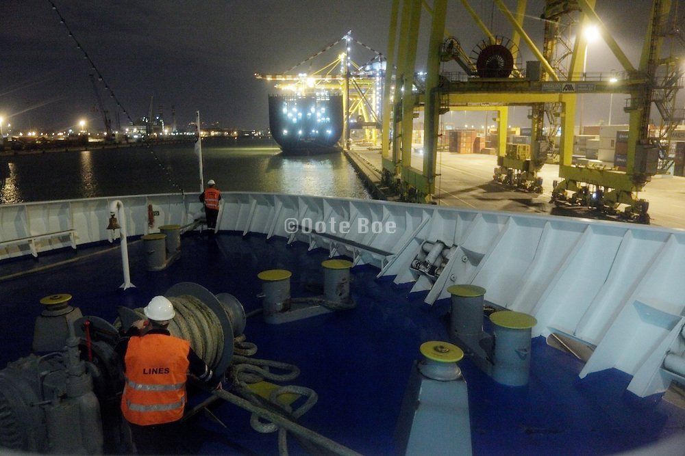 lines workers on front of large ship during night time