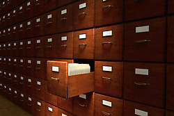 Open file drawer in a dark room filled with file cabinets