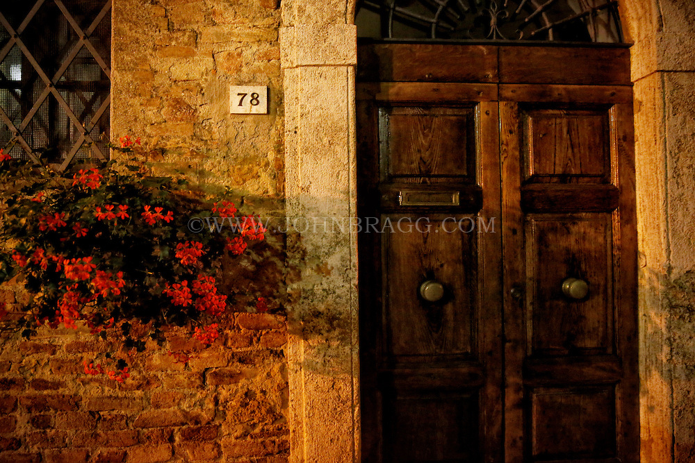Photo taken at dusk of a doorway with vibrant red flowers in Pienza, Italy.