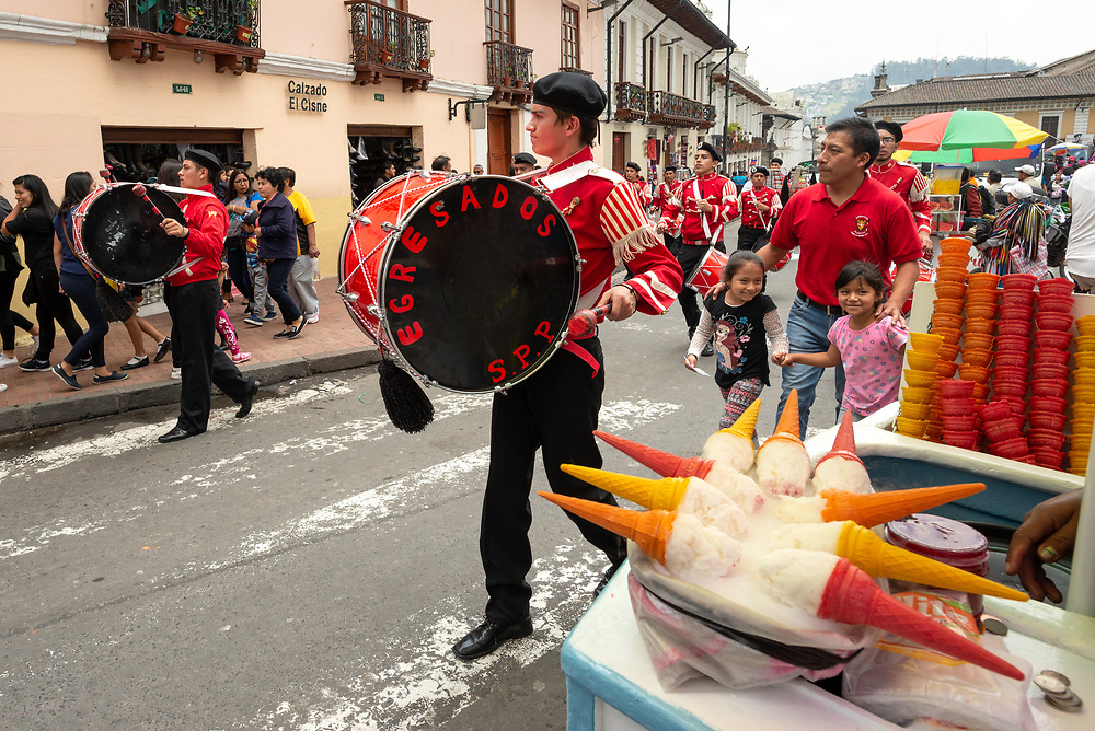 Marching band passing an ice cream vendor in the old city of Quito, Ecuador.