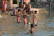 People bathing in shallow water of the Hoogly river . Calcutta. India.