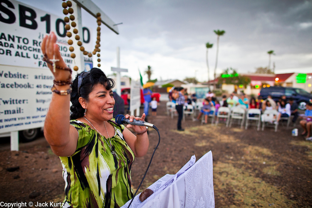 July 22 - PHOENIX, AZ: A woman leads a rosary service for opponents of SB 1070 in Phoenix. About 50 people gathered on a street corner in a Hispanic neighborhood in Phoenix, AZ, Thursday night to pray the rosary. They are members of a Catholic community that opposes Arizona's tough new immigration law, SB 1070, which requires local police officers to check the immigration status of people they suspect of being in the US illegally and requires legal immigrants in Arizona to carry their immigration documents with them at all times. Photo by Jack Kurtz