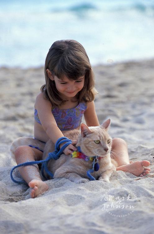 3 year old girl & cat on beach