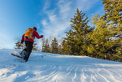 A man snowshoeing on Hanson Top on Green Mountain in Effingham, New Hampshire. Winter.