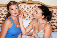 Teenage Girl sitting on bed applying blush to friend's face