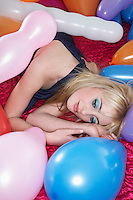 Teenage girl (16-17) lying on bed surrounded by balloons