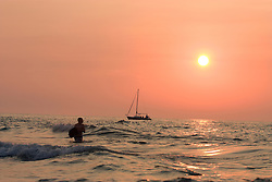 Boy playing in the surf at sunset with sailboat in background