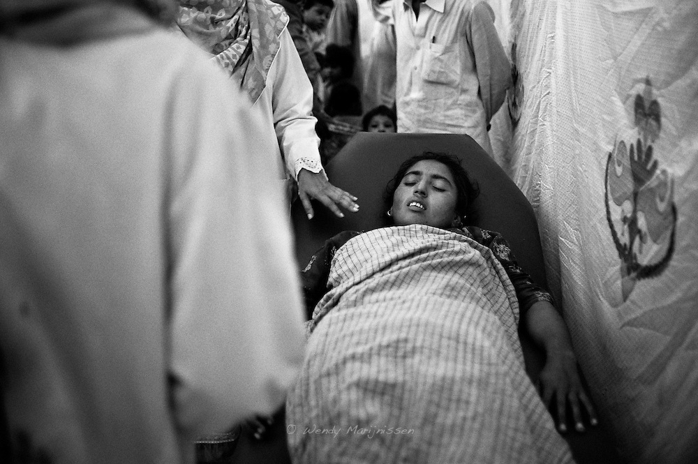 A woman feels sick and is about to faint. She is brought into the makeshift doctor's office set up to attend to the flood victims temporarely living in the Perpi storage building. Doctors and midwifes provide round the clock care and free medicine. Karachi, Pakistan, 2010