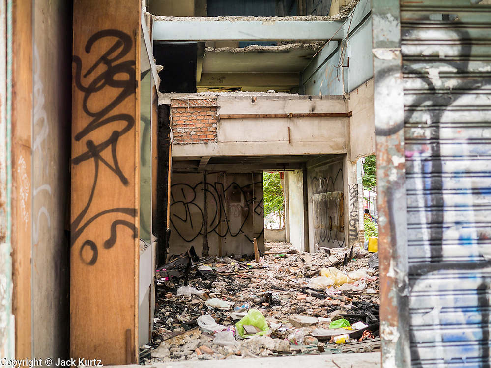 16 OCTOBER 2012 - BANGKOK, THAILAND: Looking into an abandoned building on Phetchaburi Rd in central Bangkok, Thailand. The building used to be an optician's shop with residences above the ground floor shop. The global economic slowdown had little visible effect in Bangkok. Construction projects dot the city of 12 million and development continues unabated.    PHOTO BY JACK KURTZ