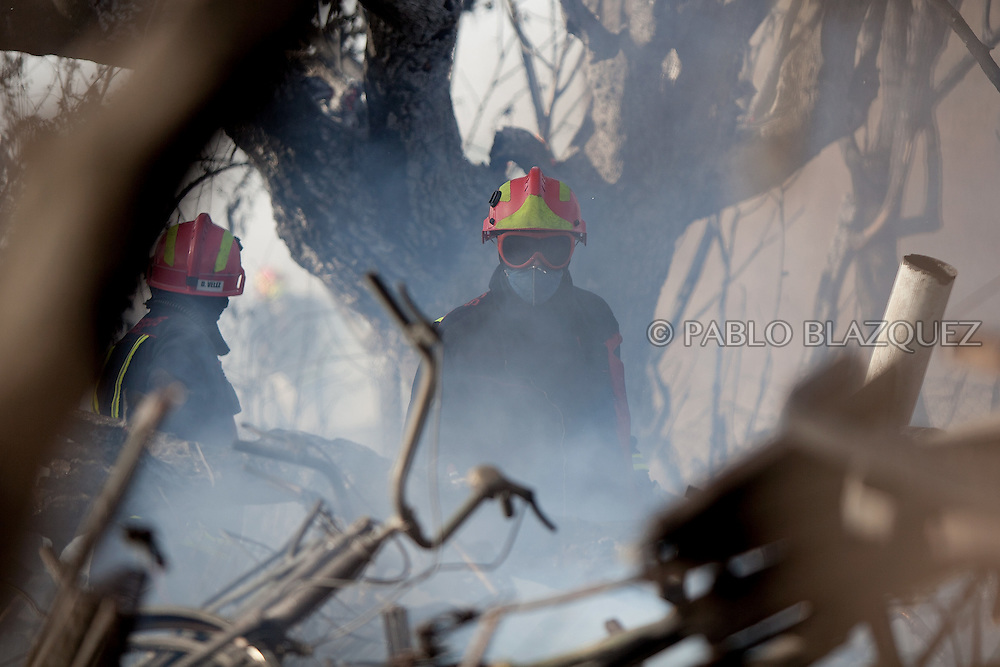 A Madrid Community firefighter works on a forest fire that reached a house in San Agustin de Guadalix on August 11, 2012, near Madrid, Spain. During a heat wave dozens of forest fires have appeared in Spain, three of them at National Parks, like Teide, Doñana or Cabañeros, and also thousands of people had to be evacuated at La Gomera and Tenerife, in the Canary Islands.