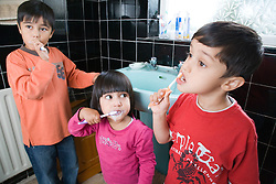 Brothers and sister brushing their teeth together,